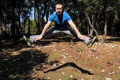 L'uomo che fa il salto di allenamento su nell'esercizio di aria in abiti sportivi d'uso dello sportivo bello della foresta sta sa Immagini Stock Libere da Diritti