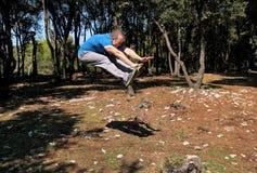 L'uomo che fa il salto di allenamento su nell'esercizio di aria in abiti sportivi d'uso dello sportivo bello della foresta sta sa Fotografie Stock Libere da Diritti