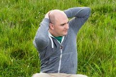 L'uomo che fare si siede aumenta su un prato verde, primo piano Fotografia Stock Libera da Diritti