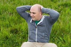 L'uomo che fare si siede aumenta su un prato verde, primo piano Fotografie Stock Libere da Diritti