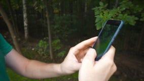 L'uomo che gioca Pokemon VA l'applicazione lo Smart Phone app della realtà aumentato colpo mentre prova a prendere Pokemon stock footage