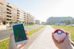 L'uomo che gioca Pokemon va tenere il pokeball Fotografie Stock