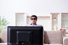 L'uomo che guarda 3d TV a casa Fotografie Stock