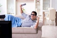 L'uomo che guarda 3d TV a casa Fotografie Stock Libere da Diritti
