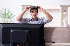 L'uomo che guarda 3d TV a casa Immagini Stock