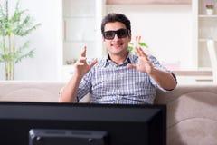 L'uomo che guarda 3d TV a casa Fotografie Stock