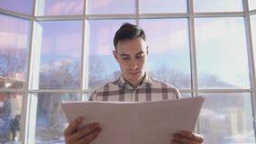 L'uomo che guarda i disegni sta su fondo della finestra in ufficio archivi video