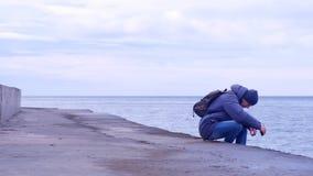 L'uomo che il turista viene a vecchio lungomare del mare si siede ed esamina il mare nell'inverno video d archivio