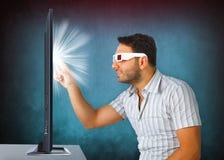 L'uomo che indossa i vetri 3d tocca la TV Fotografie Stock Libere da Diritti