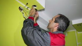L'uomo che installa il soffitto ha condotto la luce archivi video