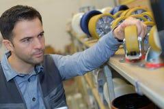 L'uomo che ispeziona il carrello spinge dentro la fabbrica Fotografie Stock Libere da Diritti