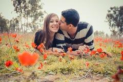 L'uomo che la bacia la donna ed ha un sorriso a trentadue denti mentre essi che pongono la o Fotografia Stock