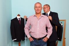L'uomo che misura per la a ha annunciato il vestito Immagine Stock