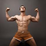 L'uomo che mostra i suoi muscoli gradisce un vincitore fotografia stock libera da diritti