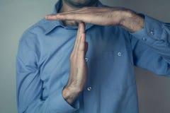L'uomo che mostra il tempo fuori gesture immagine stock