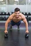 L'uomo che muscolare fare spinge aumenta con le campane del bollitore in palestra Fotografia Stock Libera da Diritti