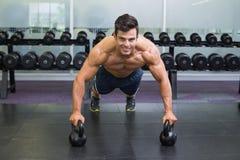 L'uomo che muscolare fare spinge aumenta con le campane del bollitore in palestra Fotografia Stock