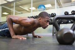 L'uomo che muscolare senza camicia fare spinge aumenta in palestra Fotografia Stock Libera da Diritti