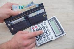 L'uomo che per mezzo del calcolatore e calcola i soldi in Ministero degli Interni fotografia stock libera da diritti