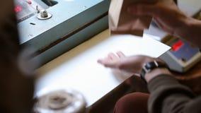 L'uomo che per mezzo della macchina ha progettato specialmente per dispensare e caffè del pacchetto per offrire l'alta qualità de stock footage
