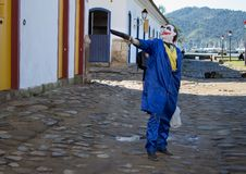 L'uomo che porta un costume blu sta tenendo un'arma immagini stock
