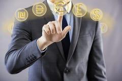 L'uomo che preme i bottoni con differenti valute Immagini Stock Libere da Diritti