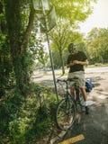 l'uomo che prende una pausa dalla bicicletta di guida controlla il telefono Immagine Stock