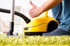 L'uomo che pulisce il tappeto del pavimento con una fine dell'aspirapolvere su fotografie stock libere da diritti