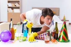 L'uomo che pulisce la casa dopo la festa di Natale Fotografie Stock