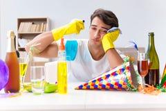 L'uomo che pulisce la casa dopo la festa di Natale Fotografia Stock Libera da Diritti