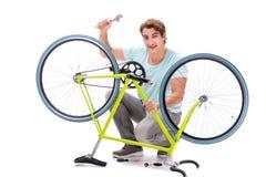 L'uomo che ripara la sua bici isolata su fondo bianco fotografia stock libera da diritti