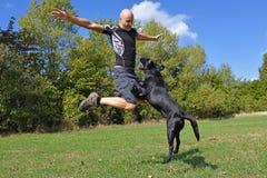 L'uomo che salta con il cane Immagini Stock