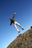 L'uomo che salta con le braccia spalancate Immagine Stock
