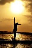 L'uomo che salta contro il tramonto sulla spiaggia fotografia stock libera da diritti