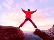 L'uomo che salta dal bordo della montagna Uomo che salta giù una scogliera senza corda Momento rischioso immagini stock