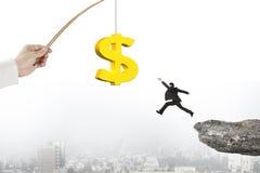 L'uomo che salta il richiamo dorato di pesca del simbolo di dollaro con paesaggio urbano della scogliera Fotografia Stock Libera da Diritti