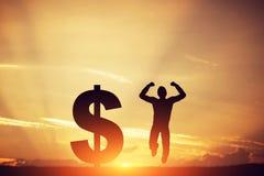 L'uomo che salta per la gioia accanto al simbolo del dollaro vincitore Immagini Stock