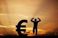 L'uomo che salta per la gioia accanto all'EURO simbolo vincitore Immagine Stock Libera da Diritti