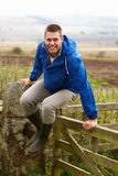 L'uomo che salta sopra il cancello del paese Fotografia Stock Libera da Diritti