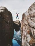 L'uomo che salta sopra il viaggio di Kjeragbolten in Norvegia Fotografia Stock