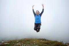 L'uomo che salta sul picco di montagna Immagini Stock