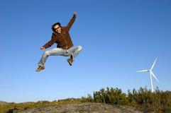 L'uomo che salta sulle rocce Immagini Stock