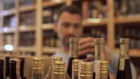 L'uomo che sceglie vino per una cena festiva Tipo che scegliere il vino nel deposito è sfuocato Le bottiglie di vino sono stock footage