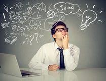 L'uomo che si siede alla tavola con il computer portatile ha molte idee che progettano il futuro Immagine Stock Libera da Diritti