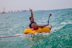 L'uomo che si siede in anello gonfiabile rimorchiato in barca nell'acqua e che fa i fronti alla macchina fotografica e che tiene  Fotografia Stock