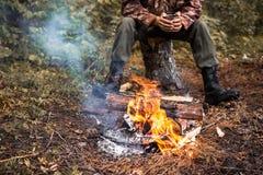 L'uomo che si siede dal fuoco nella foresta Fotografia Stock