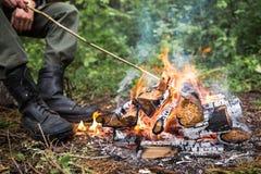 L'uomo che si siede dal fuoco nella foresta Fotografia Stock Libera da Diritti