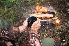 L'uomo che si siede dal fuoco nella foresta Immagini Stock Libere da Diritti