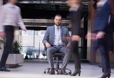 L'uomo che si siede nella sedia dell'ufficio, la gente di affari raggruppa il passaggio vicino Fotografia Stock