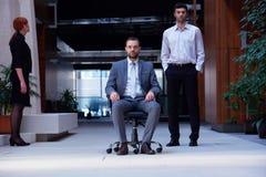 L'uomo che si siede nella sedia dell'ufficio, la gente di affari raggruppa il passaggio vicino Fotografie Stock Libere da Diritti